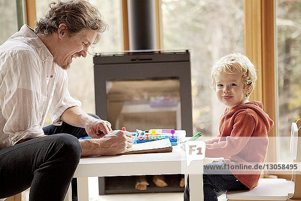 Portrait of cute boy writing at table while sitting with father in home