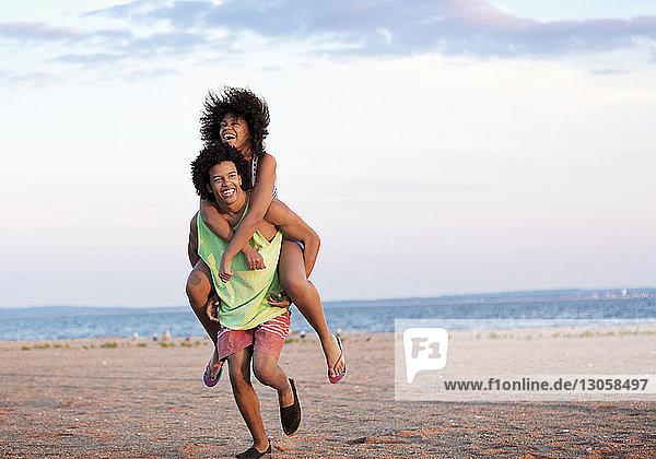 Mann nimmt Freundin am Strand huckepack gegen den Himmel