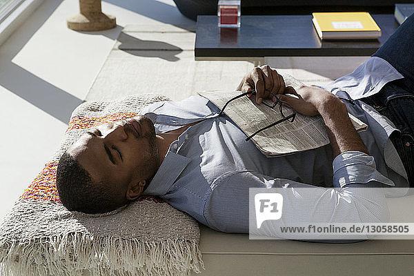 High angle view of man sleeping on sofa