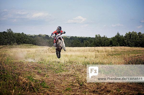 Man riding dirt bike on field