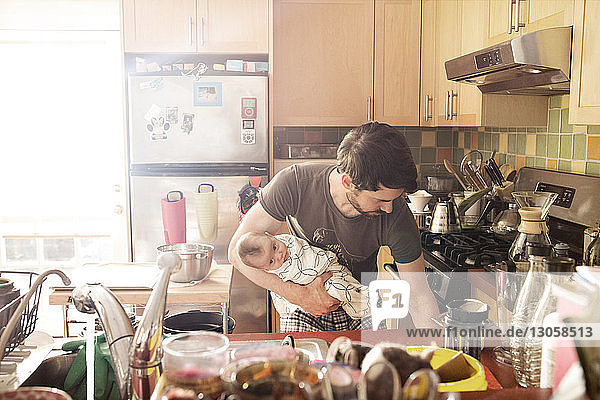 Father holding baby daughter and working in kitchen