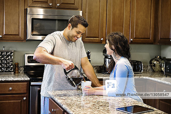 Boyfriend pouring coffee in cup while standing by woman in kitchen