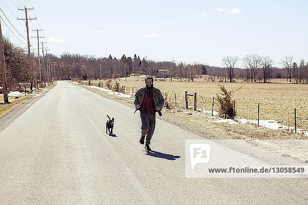 Full length of man and dog running on country road during vacation