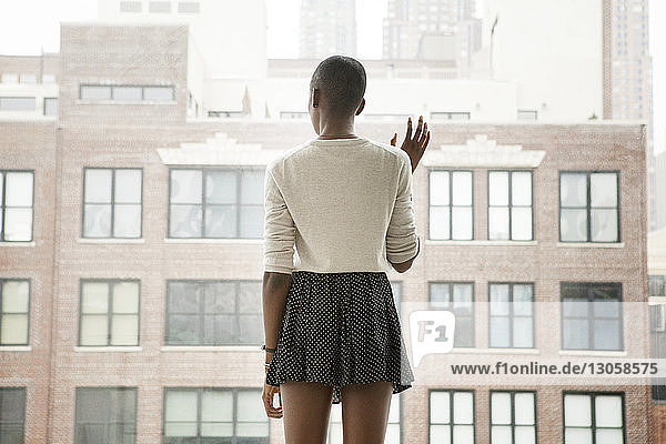 Rear view of woman standing by window at home