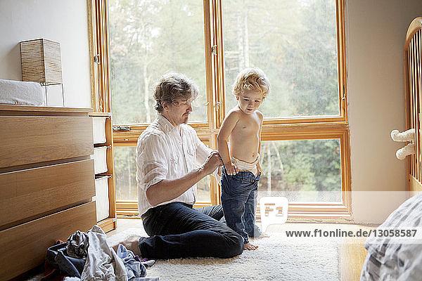 Vater kleidet Sohn an  während er zu Hause sitzt