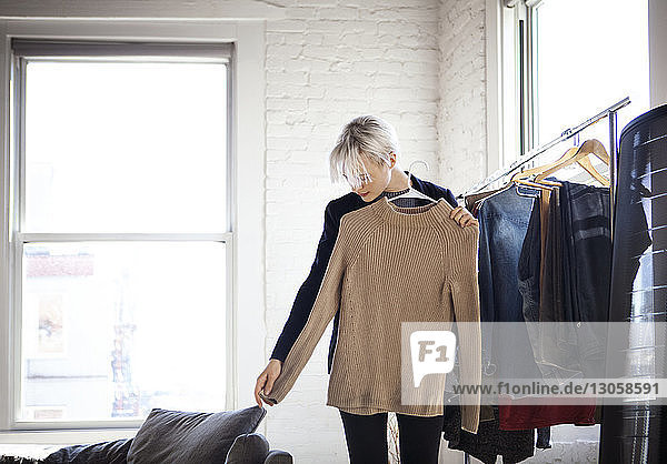 Young woman selecting clothes at home