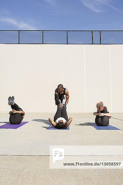 Männlicher Ausbilder  der Sportlerinnen bei der Durchführung von Übungen auf dem Feld ausbildet