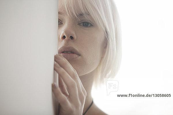 Porträt einer Frau  die sich zu Hause hinter einer Mauer versteckt