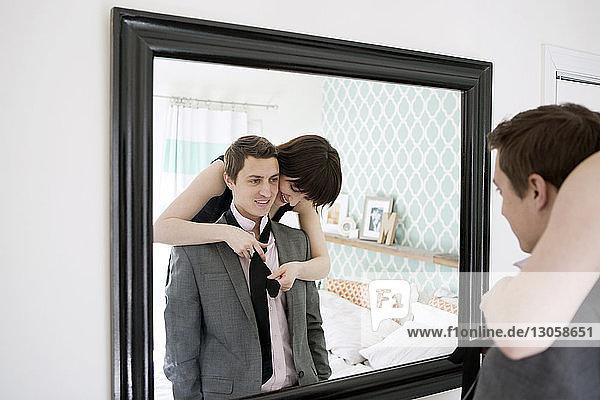 Smiling woman tying boyfriend's necktie in front of mirror