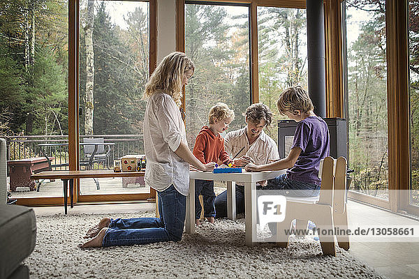 Happy family making craft at table in home