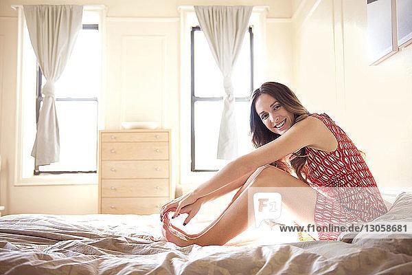 Porträt einer lächelnden Frau  die zu Hause auf dem Bett sitzt