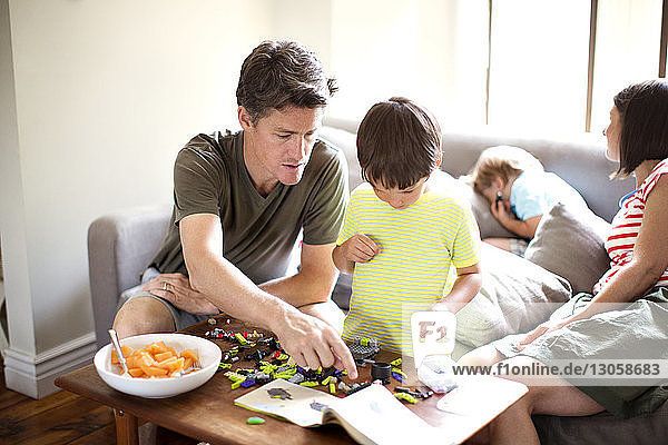 High angle view of father playing with son at table in living room