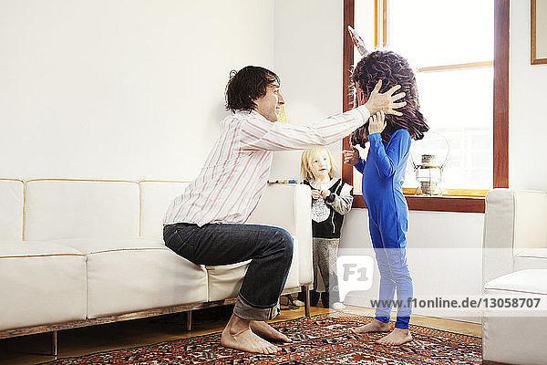 Vater hilft Sohn beim Tragen von Tierkostümen zu Hause
