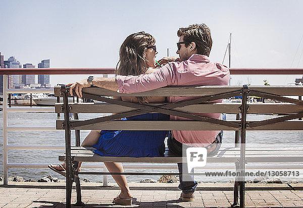 Rückansicht des auf der Bank gegen das Geländer sitzenden Paares