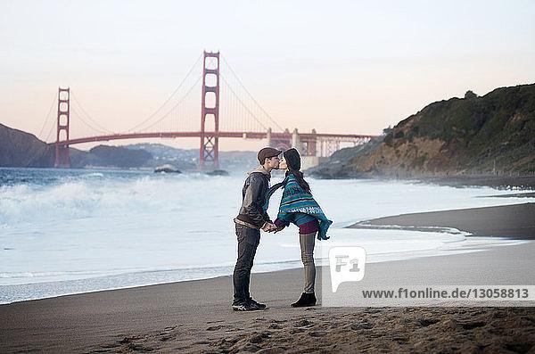 Young couple kissing on shore against Golden Gate Bridge