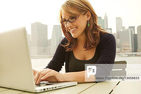 Glückliche Frau mit Laptop auf Tisch gegen Stadtbild