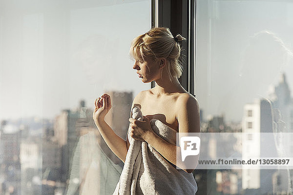 Woman wrapped in towel looking through window while standing at home