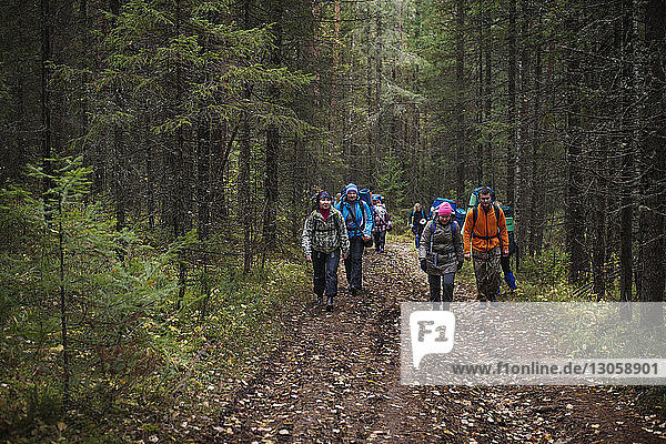 Friends walking on dirt road amidst trees in forest
