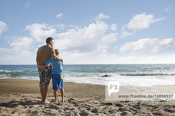 Vater und Sohn stehen am Strand gegen den Himmel