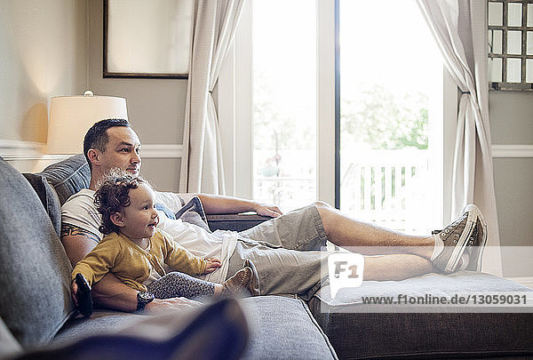 Father and daughter watching television while sitting on sofa at home