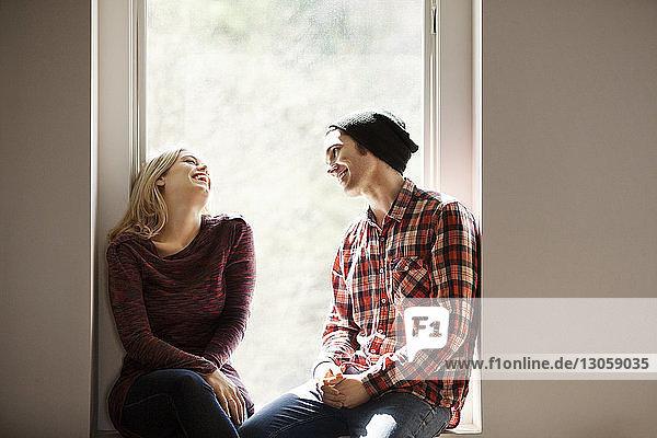 Fröhliches Paar unterhält sich auf der Fensterbank sitzend