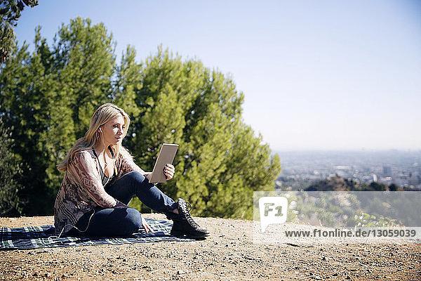 Frau benutzt Tablet-Computer  während sie auf einer Matte sitzt