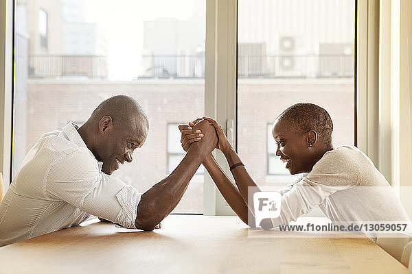 Couple playing arm wrestling while sitting by table at home