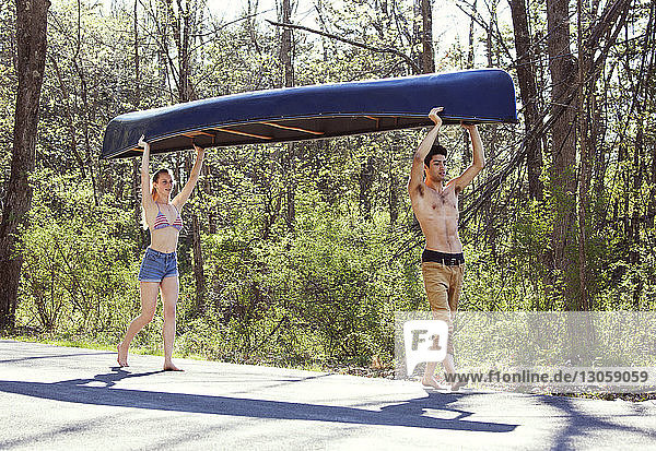 Full length of couple carrying rowboat while walking on road in forest