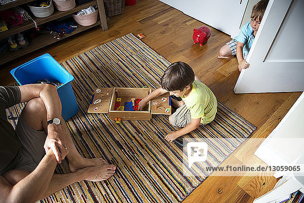 High angle view of father sitting by boys playing at home