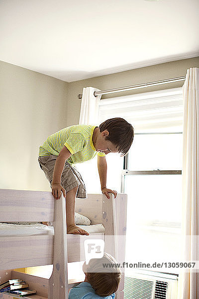 Brothers playing on bunkbed at home