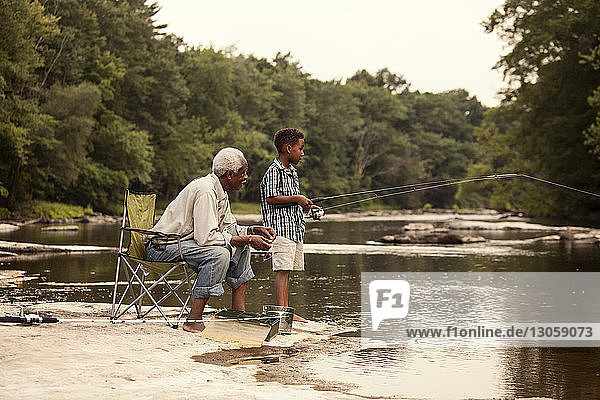 Grandfather looking at grandson fishing while sitting by lake