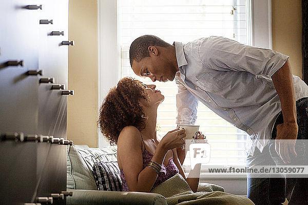 Romantische Frau hält Becher  während sie den Mann zu Hause anschaut