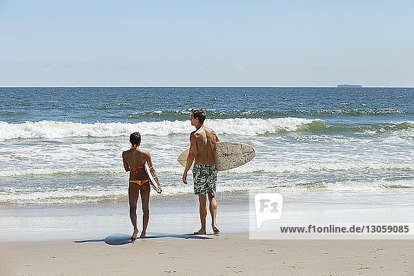 Rear view of couple carrying surfboard at beach
