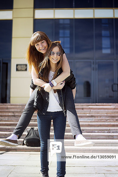 Portrait of cheerful woman giving piggyback to friend outside building