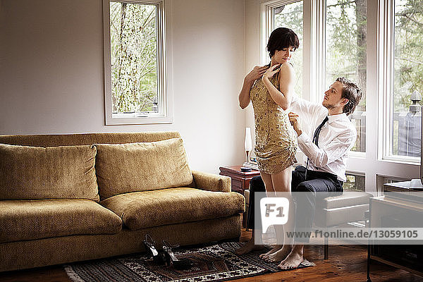 Man zipping woman's dress at home