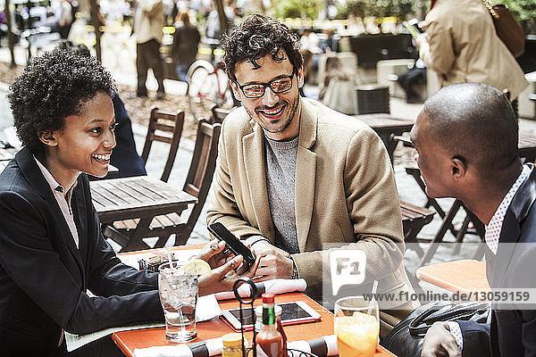 Glückliche Geschäftsfrau zeigt Geschäftsleuten ihr Smartphone  während sie im Straßencafé sitzt