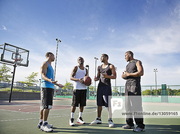 Sportsmen talking while standing in basketball court