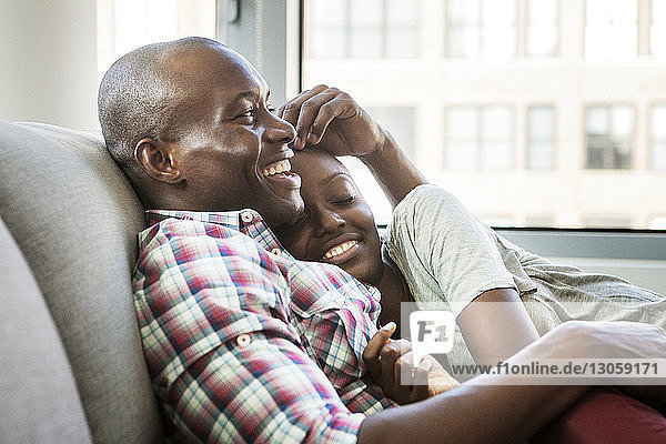Smiling couple relaxing on sofa at home