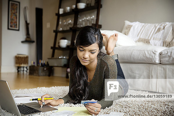 Serious woman checking bills while using laptop at home