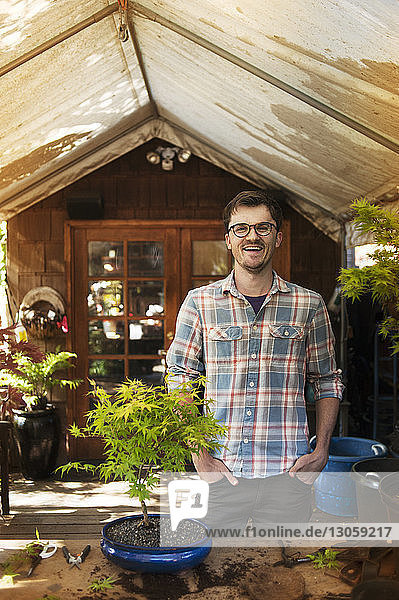 Portrait of man with potted plant standing at backyard