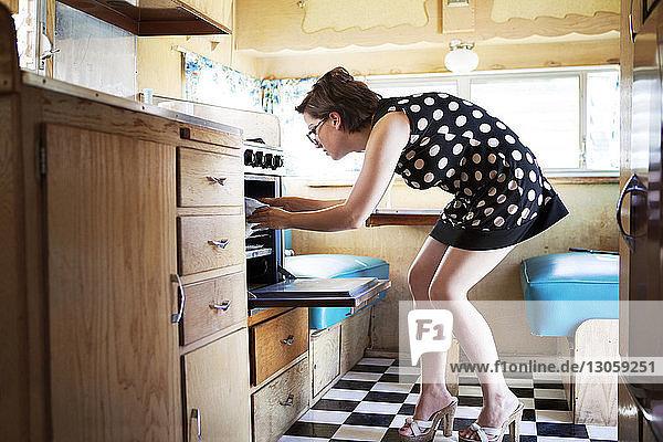 Seitenansicht einer Frau  die im Wohnmobil Lebensmittel aus dem Ofen nimmt