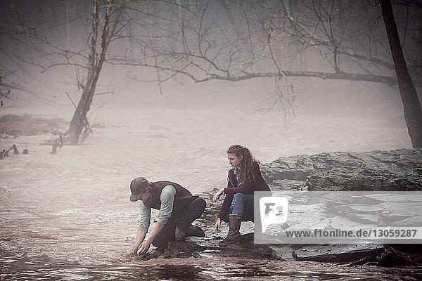 Mann wäscht Hände im Fluss mit Frau im Wald