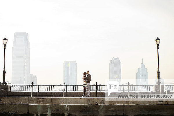 Young couple standing on footbridge against clear sky