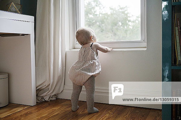 Rear view of baby girl looking through window