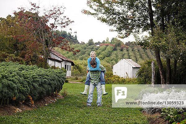 Mann nimmt Frau Huckepack auf Grasfeld