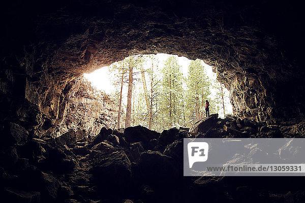 Frau steht auf Felsen in einer Höhle im Wald