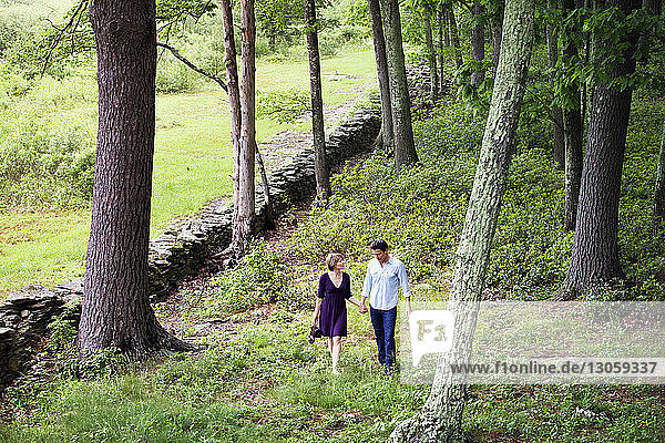 Couple holding hands while walking on field