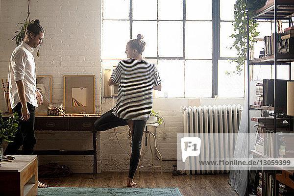 Frau macht Yoga von Mann zu Hause