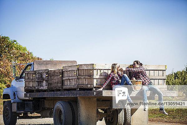Mann teilt Obst mit seiner Freundin  während er auf einem Lastwagen vor klarem Himmel sitzt