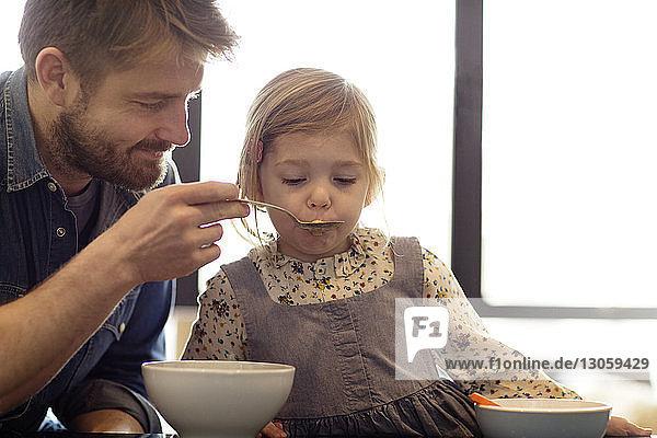 Vater füttert Tochter mit Löffel zu Hause